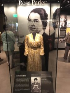 Image of the display honoring Rosa Parks. Display has a plaque that discusses her activism, and one of her dresses she wore.
