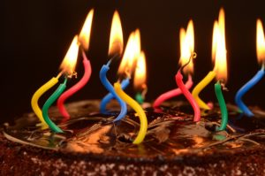 Image description: Top of a chocolate cake with candles lit. Candles are curved and multi-colored.