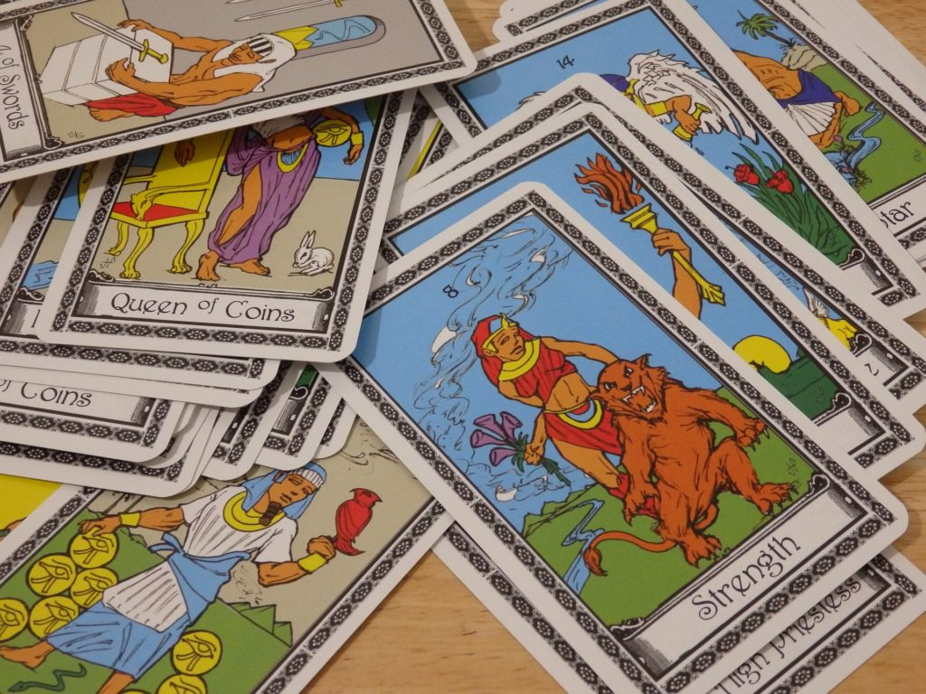 Image of tarot cards faced up and spread out on a table.